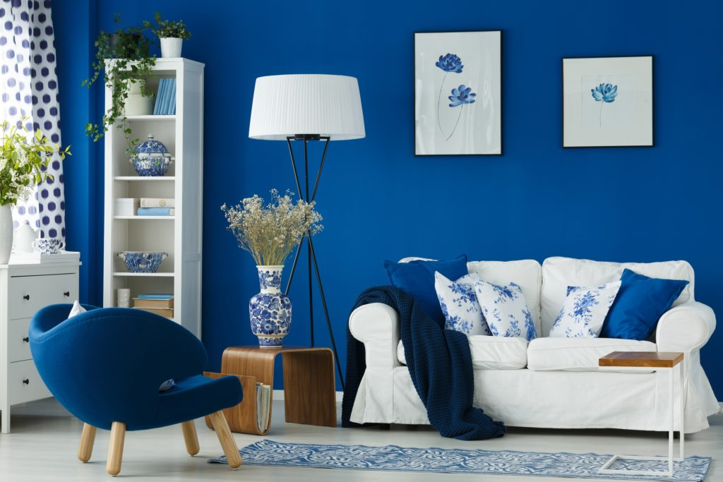 White sofa in blue living room with porcelain accessories