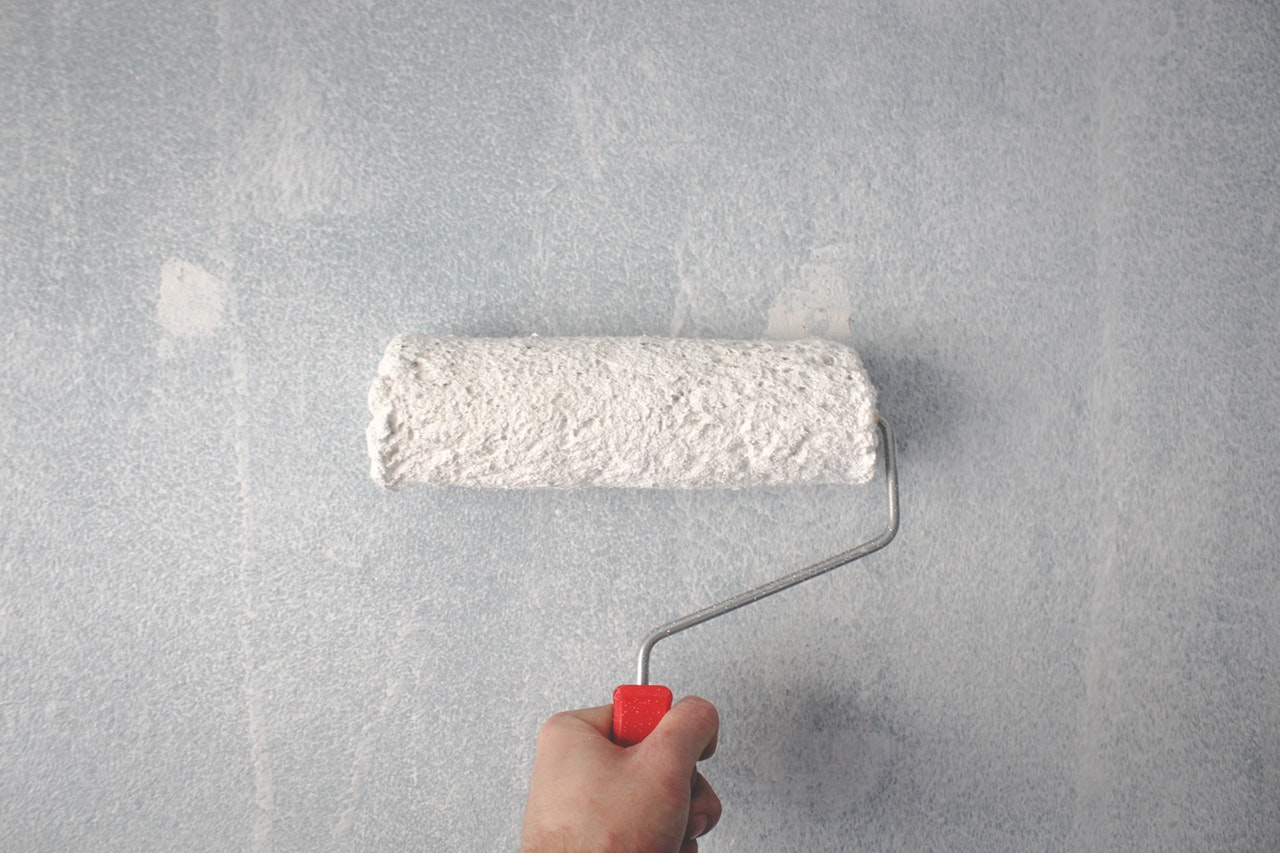 person-holding-paint-roller-on-wall-1669754